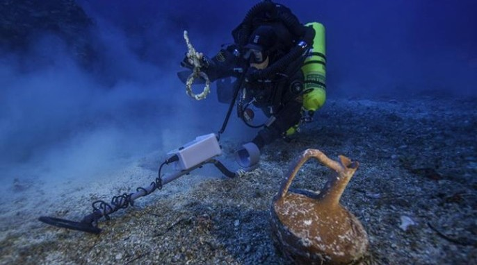 Greek technical diver Alexandros Sotiriou discovers an intact ceramic table jug and a bronze rigging ring on the Antikythera Shipwreck. (Brett Seymour, Return to Antikythera 2014)