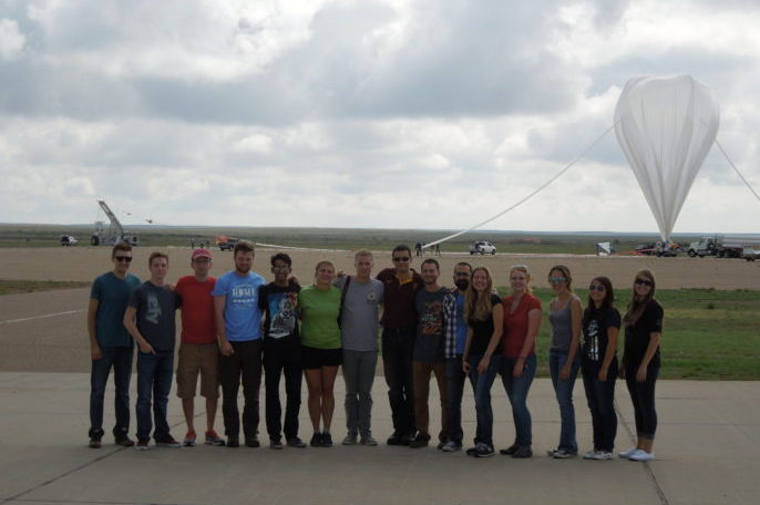 Science Experiments: Students attending the 2016 High-Altitude Student Platform launch in Fort Sumner, N.M., pose in front of the fully inflated scientific balloon just prior to lift-off. Credits: Louisiana Space Consortium/T.G. Guzik