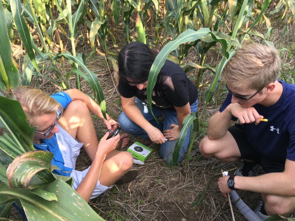 Three youth volunteers in the middle of an agricultural field testing the soil quality using scientific tools as part of the MO Dirt program.